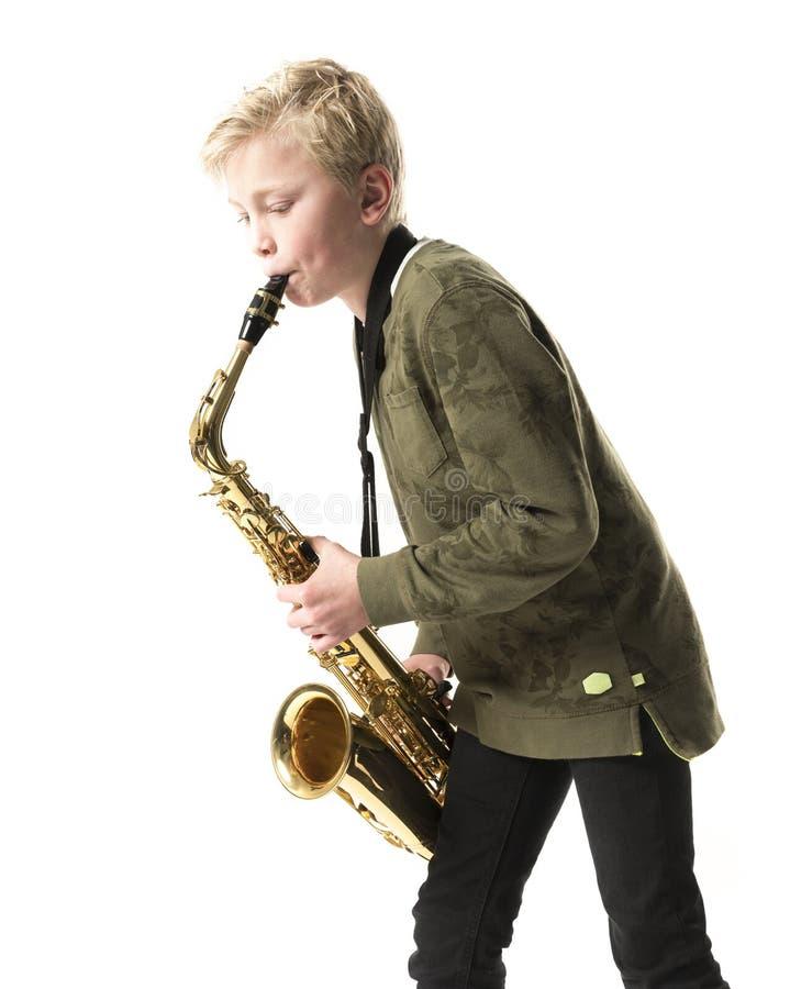 Νέα ξανθά αγόρι και saxophone στο στούντιο στοκ φωτογραφία