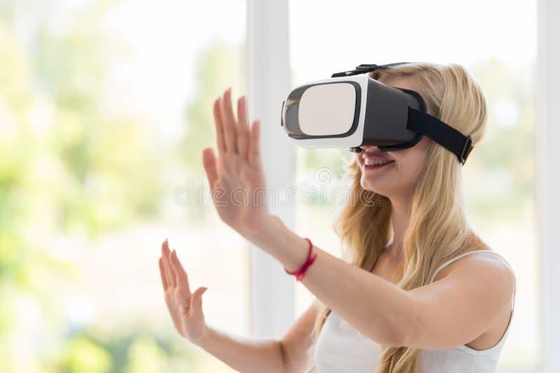 Νέα ξανθά γυαλιά εικονικής πραγματικότητας ένδυσης γυναικών ψηφιακά, ευτυχές χαμογελώντας όμορφο κορίτσι στοκ φωτογραφία με δικαίωμα ελεύθερης χρήσης