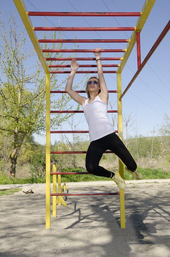 Νέα ξανθή άσκηση γυναικών στο πάρκο στοκ φωτογραφία με δικαίωμα ελεύθερης χρήσης