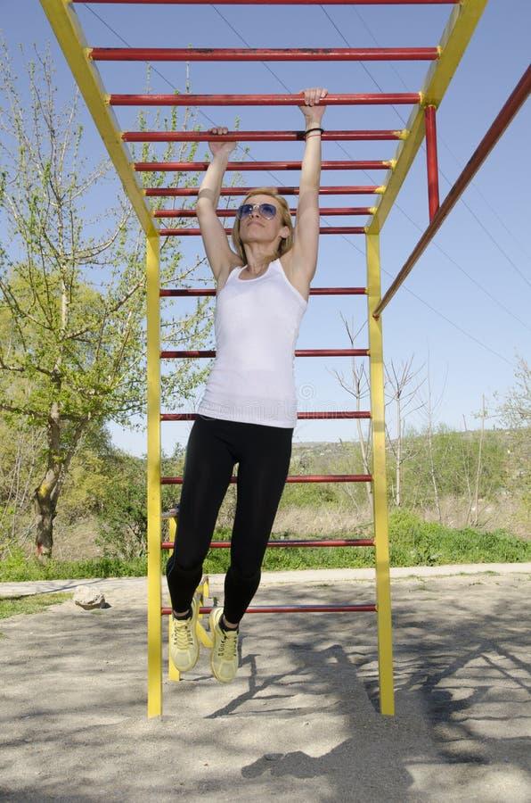 Νέα ξανθή άσκηση γυναικών στο πάρκο στοκ φωτογραφίες με δικαίωμα ελεύθερης χρήσης