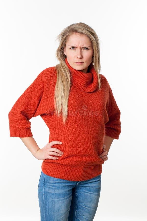 νέα ξανθή γυναίκα με τα χέρια να κοιτάξει επίμοναη και των δύο ισχίων στοκ εικόνες
