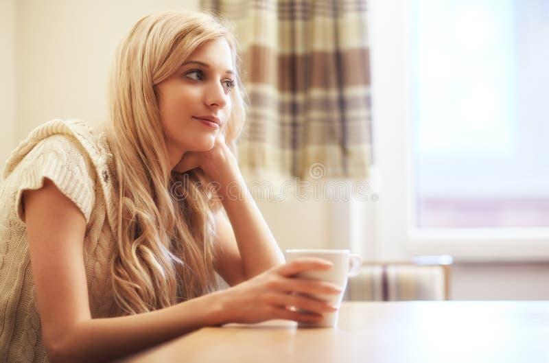 Νέα ξανθή γυναίκα με το φλυτζάνι καφέ στον πίνακα στοκ φωτογραφία