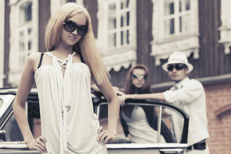Νέα ξανθή γυναίκα μόδας στο άσπρο φόρεμα δίπλα στο αναδρομικό αυτοκίνητο στοκ φωτογραφίες