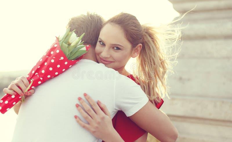 Νέα ξανθή γυναίκα που αγκαλιάζει τον άνδρα κατά την ημερομηνία στοκ εικόνα με δικαίωμα ελεύθερης χρήσης