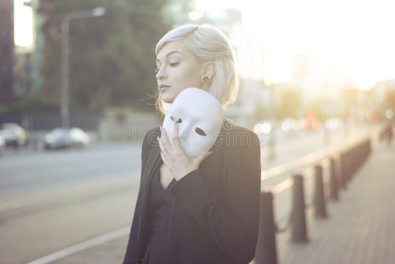 Νέα ξανθή γυναίκα που βγάζει μια μάσκα Προσπομένος για να είναι κάποιος άλλος την έννοια υπαίθρια στο ηλιοβασίλεμα στοκ φωτογραφίες με δικαίωμα ελεύθερης χρήσης
