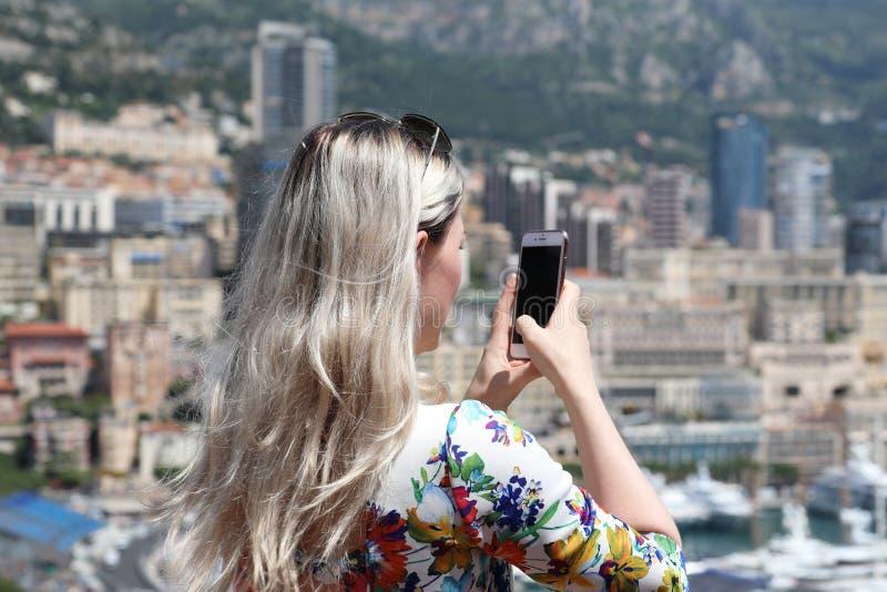 Νέα ξανθή γυναίκα που παίρνει μια εικόνα με το Smartphone της σε Monac στοκ φωτογραφία με δικαίωμα ελεύθερης χρήσης