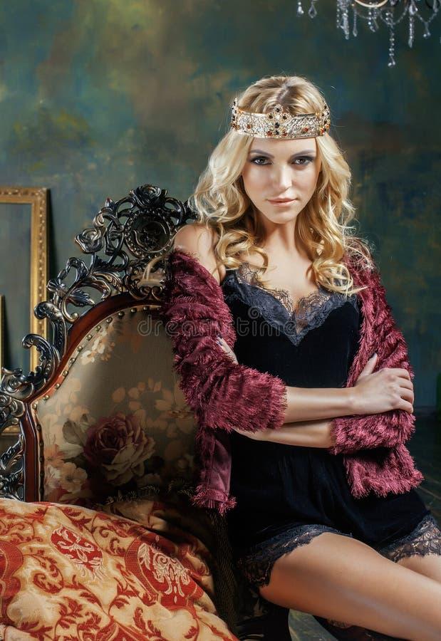 Νέα ξανθή γυναίκα που φορά την κορώνα στο εσωτερικό πολυτέλειας νεράιδων με τον κενό παλαιό συνολικό πλούτο πλαισίων, μαγική πλού στοκ φωτογραφίες