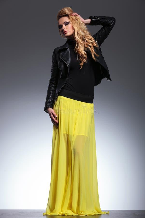 Νέα ξανθή γυναίκα σε ένα κίτρινο σακάκι φορεμάτων και δέρματος στοκ εικόνες με δικαίωμα ελεύθερης χρήσης
