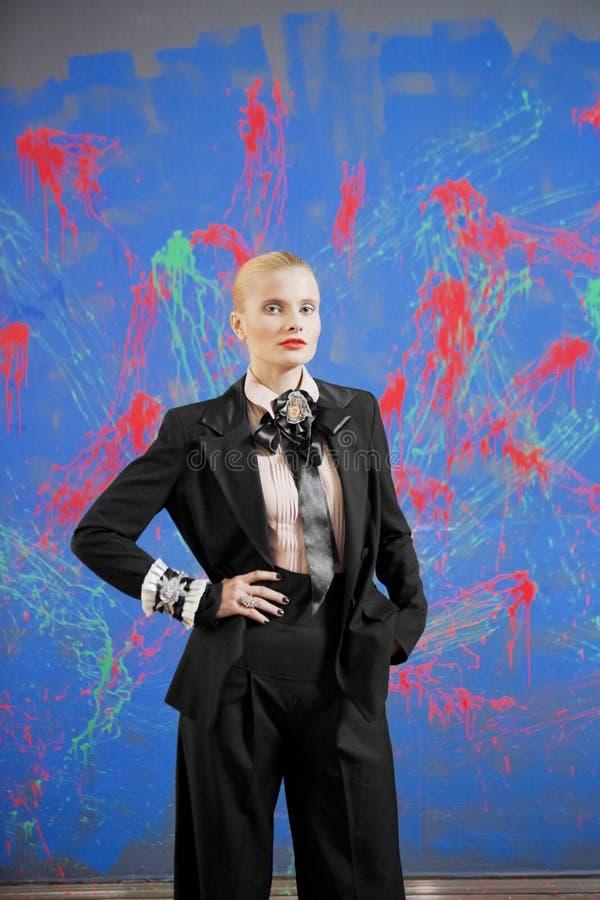 Νέα ξανθή γυναίκα σε ένα μοντέρνο κοστούμι ενάντια στον τοίχο grunge στοκ φωτογραφίες με δικαίωμα ελεύθερης χρήσης