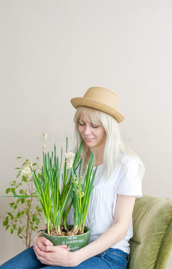 Νέα ξανθή γυναίκα στη συνεδρίαση καπέλων αχύρου στην καρέκλα με το λουλούδι στο εσωτερικό στοκ φωτογραφία με δικαίωμα ελεύθερης χρήσης