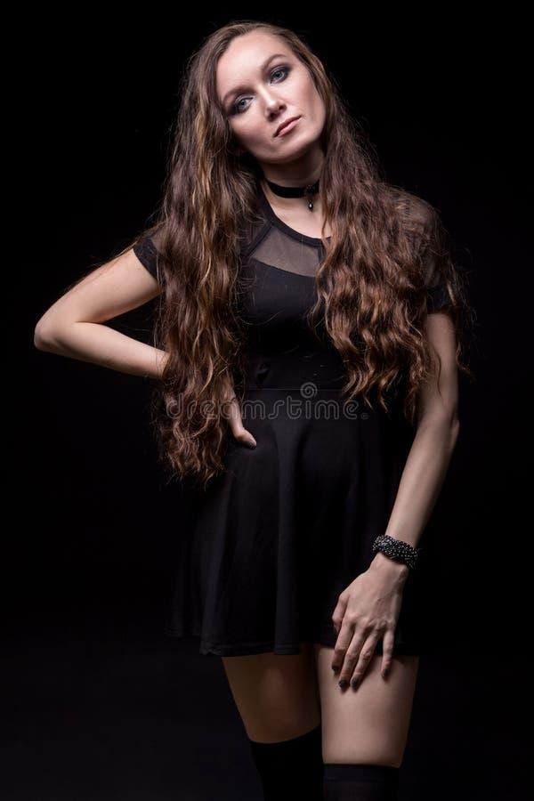 Νέα ξανθή γυναίκα στο απότομα μαύρο φόρεμα στοκ εικόνα
