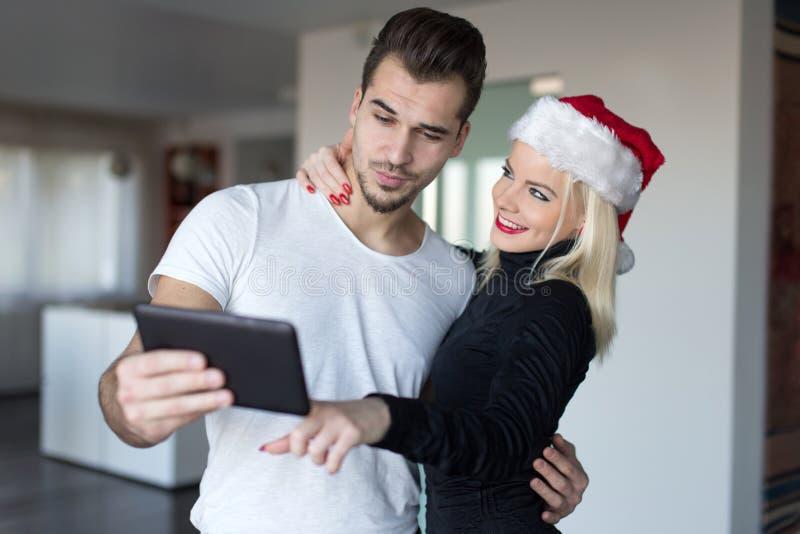 Νέα ξανθή γυναίκα στο καπέλο santa που ψωνίζει on-line για τα WI Χριστουγέννων στοκ φωτογραφία