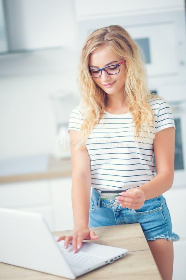 Νέα ξανθή πιστωτική κάρτα εκμετάλλευσης γυναικών και χρησιμοποίηση του φορητού προσωπικού υπολογιστή στην εγχώρια κουζίνα στοκ εικόνες με δικαίωμα ελεύθερης χρήσης