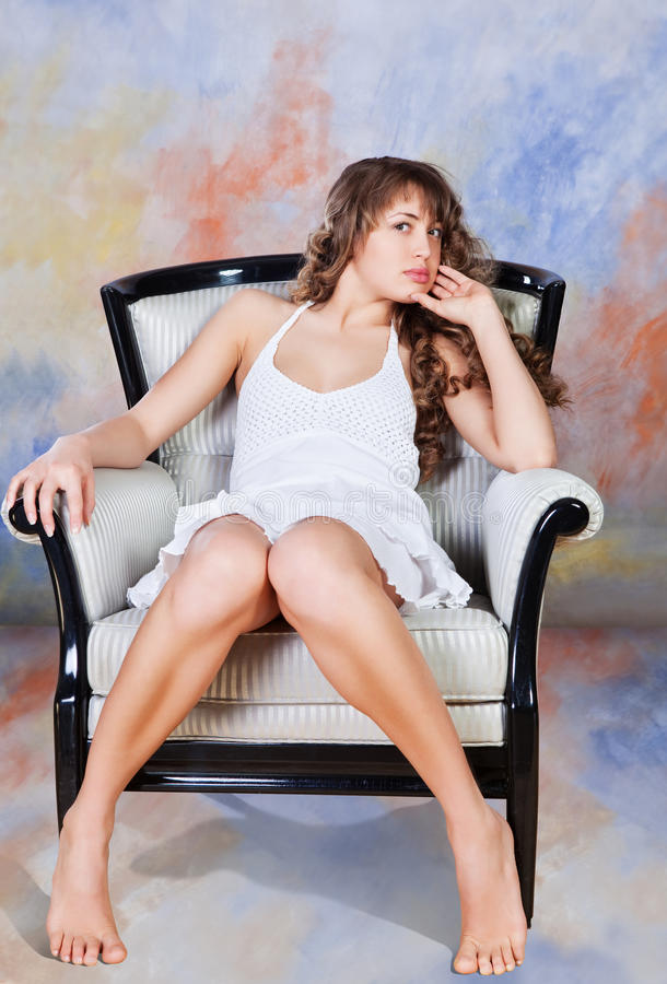 Νέα ξανθή συνεδρίαση γυναικών στην έδρα στοκ φωτογραφία με δικαίωμα ελεύθερης χρήσης