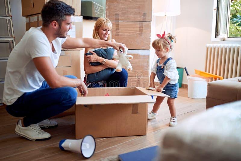 Νέα οικογένεια μετά από να αγοράσει τα ανοίγοντας κιβώτια καινούργιων σπιτιών στοκ φωτογραφία