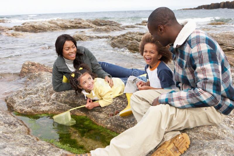 Νέα οικογένεια με το δίχτυ του ψαρέματος στους βράχους στοκ φωτογραφίες