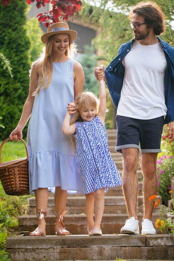 Νέα οικογένεια με το καλάθι μετά από το πικ-νίκ που περπατά κάτω από τα σκαλοπάτια έξω στο πράσινο πάρκο στοκ φωτογραφία με δικαίωμα ελεύθερης χρήσης
