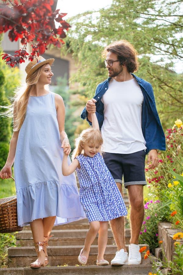 Νέα οικογένεια με το καλάθι μετά από το πικ-νίκ που περπατά κάτω από τα σκαλοπάτια έξω στο πράσινο πάρκο στοκ εικόνα με δικαίωμα ελεύθερης χρήσης