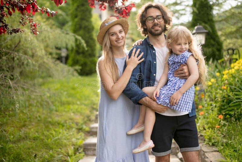Νέα οικογένεια με το καλάθι μετά από το πικ-νίκ που περπατά κάτω από τα σκαλοπάτια έξω στο πράσινο πάρκο στοκ εικόνες