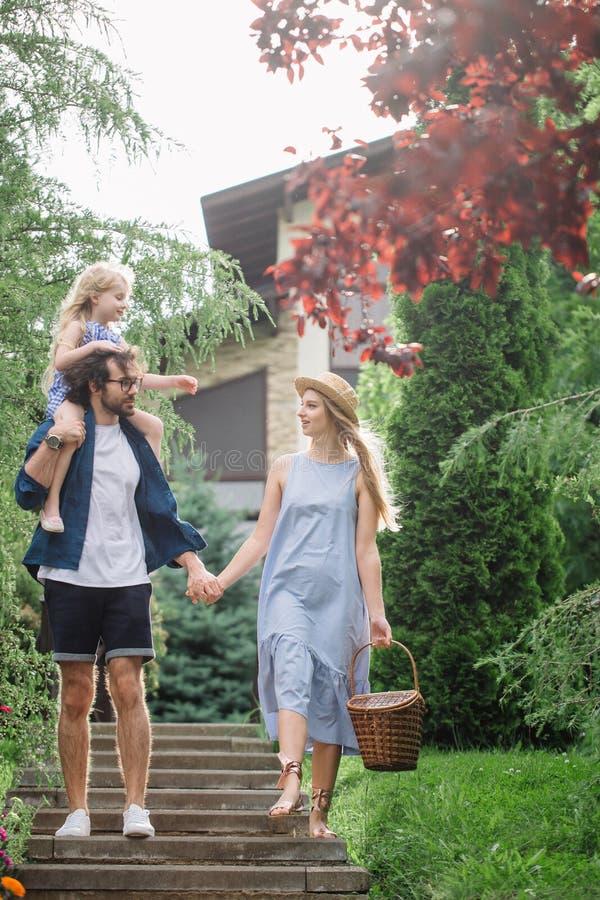Νέα οικογένεια με το καλάθι μετά από το πικ-νίκ που περπατά κάτω από τα σκαλοπάτια έξω στο πράσινο πάρκο στοκ εικόνα