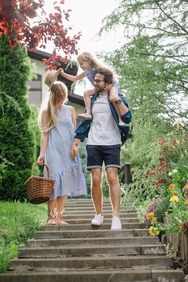 Νέα οικογένεια με το καλάθι μετά από το πικ-νίκ που περπατά κάτω από τα σκαλοπάτια έξω στο πράσινο πάρκο στοκ φωτογραφία