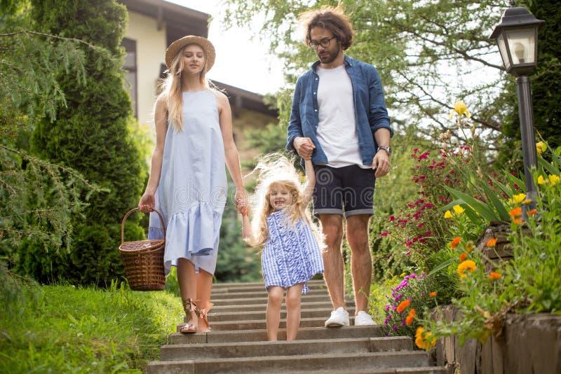 Νέα οικογένεια με το καλάθι μετά από το πικ-νίκ που περπατά κάτω από τα σκαλοπάτια έξω στο πράσινο πάρκο στοκ εικόνες με δικαίωμα ελεύθερης χρήσης