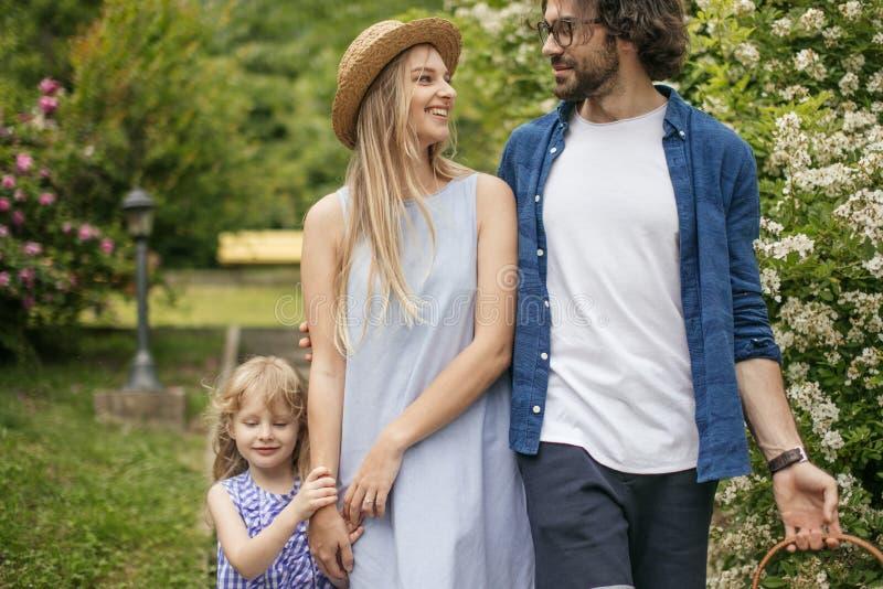 Νέα οικογένεια με το καλάθι μετά από το πικ-νίκ που περπατά κάτω από τα σκαλοπάτια έξω στο πράσινο πάρκο στοκ φωτογραφίες με δικαίωμα ελεύθερης χρήσης