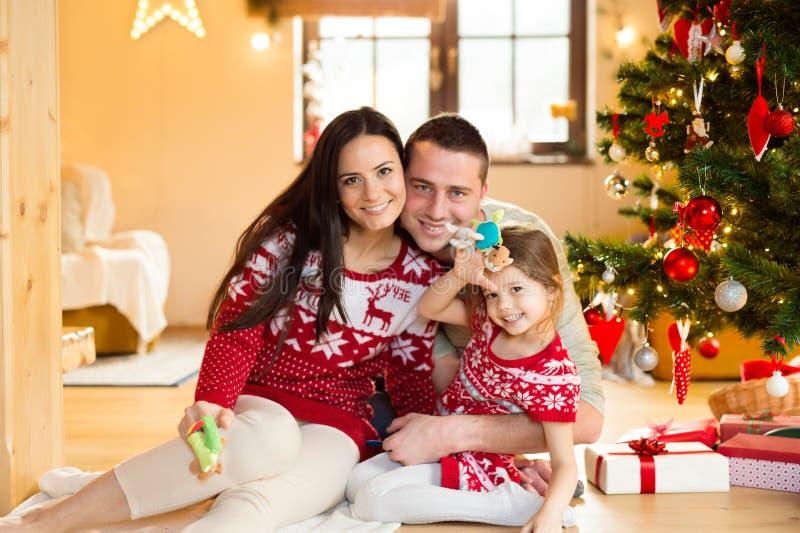 Νέα οικογένεια με το daugter στο χριστουγεννιάτικο δέντρο στο σπίτι στοκ εικόνες