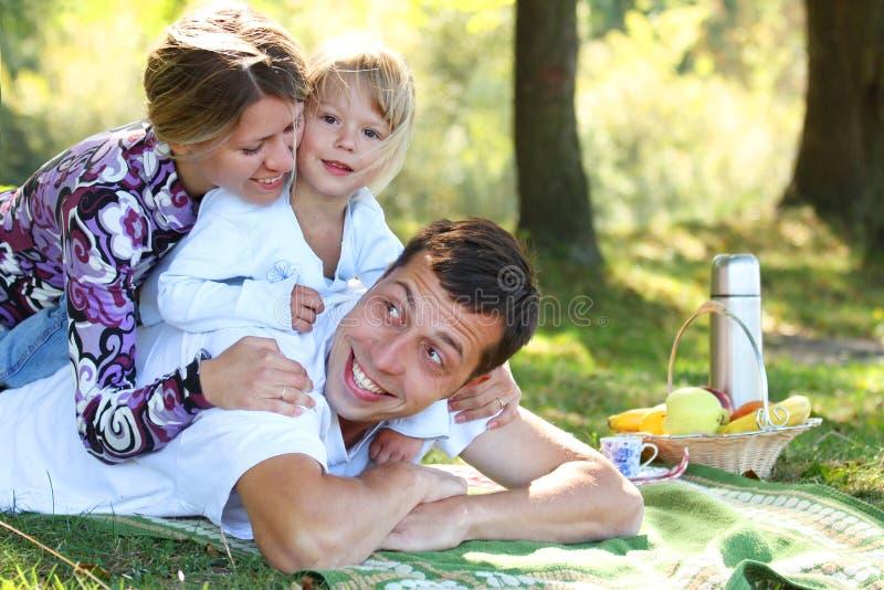 Νέα οικογένεια που έχει ένα πικ-νίκ στη φύση στοκ εικόνες με δικαίωμα ελεύθερης χρήσης