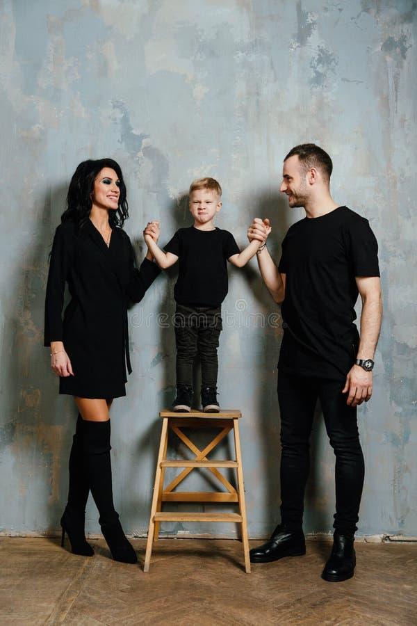 Νέα οικογένεια που έχει τη διασκέδαση στο σπίτι σε ένα υπόβαθρο ενός εκλεκτής ποιότητας κατασκευασμένου τοίχου στοκ εικόνα