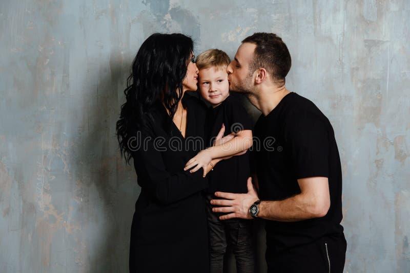 Νέα οικογένεια που έχει τη διασκέδαση στο σπίτι σε ένα υπόβαθρο ενός εκλεκτής ποιότητας κατασκευασμένου τοίχου στοκ εικόνα με δικαίωμα ελεύθερης χρήσης