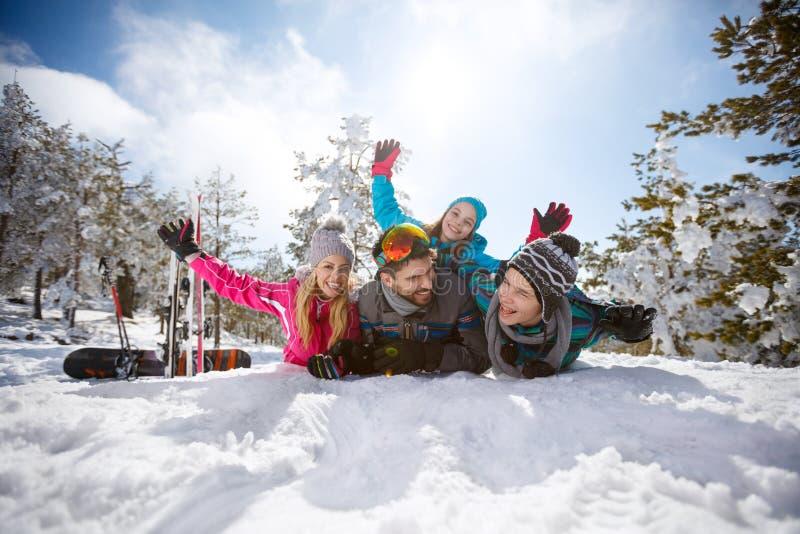 Νέα οικογένεια που έχει τη διασκέδαση στο χιόνι στο βουνό στοκ εικόνα με δικαίωμα ελεύθερης χρήσης