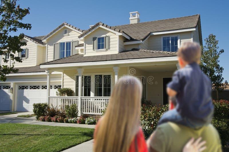 Νέα οικογένεια που εξετάζει ένα νέο σπίτι στοκ εικόνες με δικαίωμα ελεύθερης χρήσης