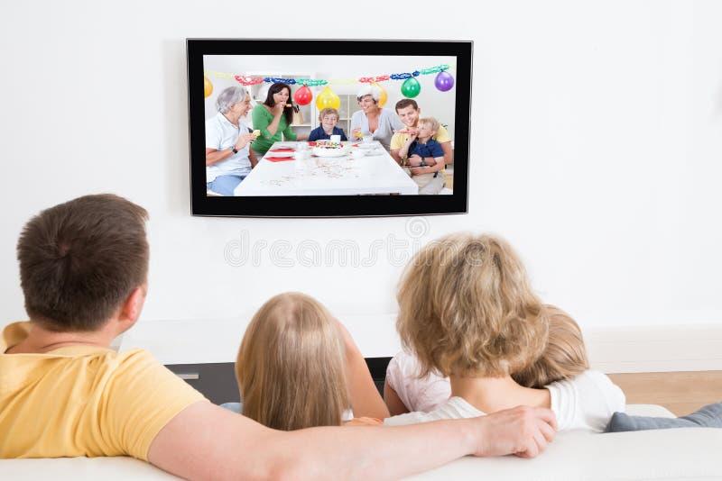 Νέα οικογένεια που προσέχει τη TV από κοινού στοκ εικόνα