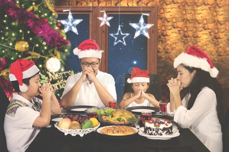Νέα οικογένεια που προσεύχεται στα Χριστούγεννα γευμάτων στοκ φωτογραφία με δικαίωμα ελεύθερης χρήσης