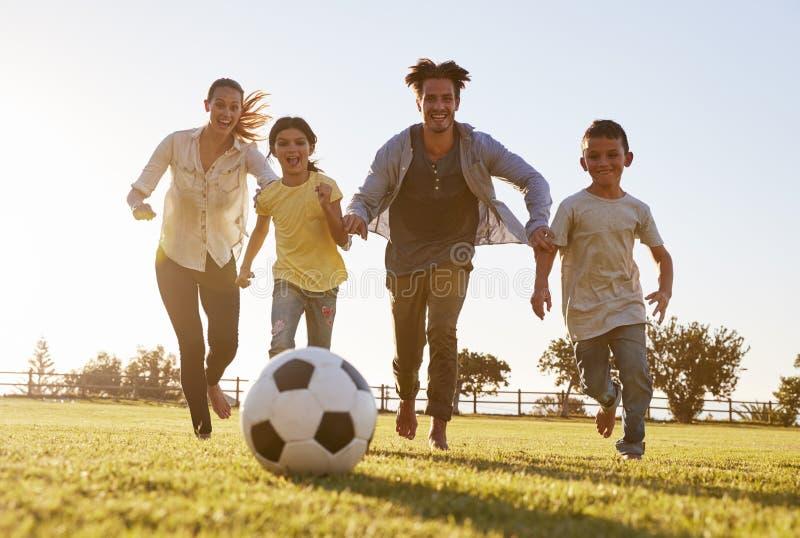 Νέα οικογένεια που χαράζει μετά από ένα ποδόσφαιρο σε ένα πάρκο στοκ εικόνες