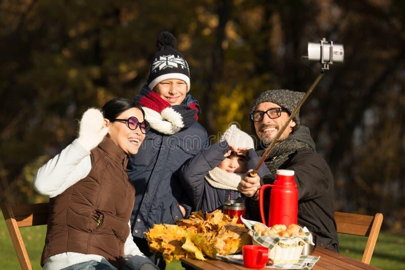Νέα οικογένεια σε ένα πικ-νίκ που κάνει selfies στοκ φωτογραφία με δικαίωμα ελεύθερης χρήσης