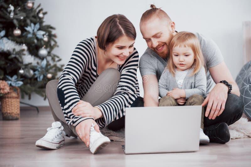 Νέα οικογένεια τριών χρησιμοποιώντας το lap-top στον τάπητα στο σπίτι στοκ εικόνα με δικαίωμα ελεύθερης χρήσης