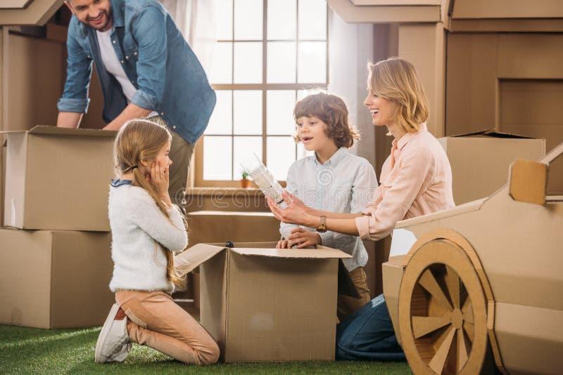 νέα οικογενειακά ανοίγοντας κιβώτια κινούμενα σε νέο στοκ εικόνες