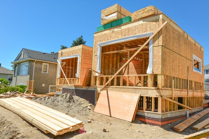 Νέα οικογενειακή κατοικία κάτω από την κατασκευή με τους σωρούς των πινάκων ξυλείας 2x4 στην κορυφή στοκ φωτογραφία