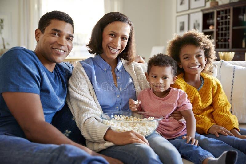 Νέα οικογενειακή συνεδρίαση αφροαμερικάνων μαζί στον καναπέ στο καθιστικό τους, που τρώει popcorn και που κοιτάζει στη κάμερα, μπ στοκ εικόνα