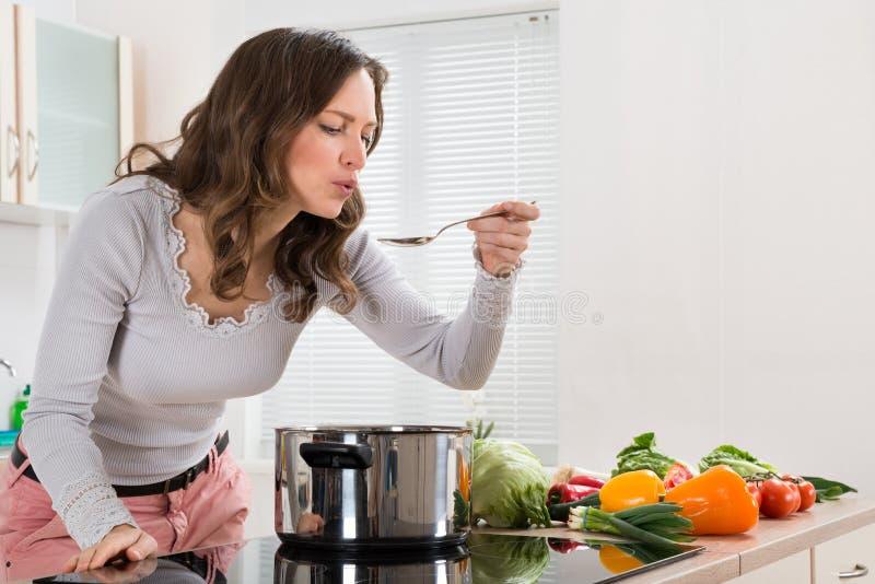 Νέα δοκιμάζοντας τρόφιμα γυναικών στοκ εικόνα με δικαίωμα ελεύθερης χρήσης