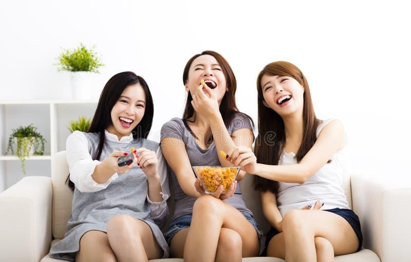νέα ομάδα γυναικών που τρώει τα πρόχειρα φαγητά και που προσέχει τη TV στοκ εικόνες με δικαίωμα ελεύθερης χρήσης