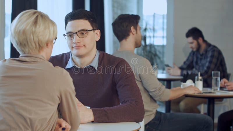 Νέα ομιλία ζευγών και καφές κατανάλωσης κοντά στο παράθυρο στον καφέ στοκ εικόνα