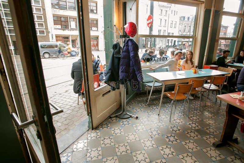 Νέα ομιλία ζευγών και μπύρα κατανάλωσης μέσα στον καφέ πόλεων με τα μεγάλα παράθυρα στοκ εικόνες