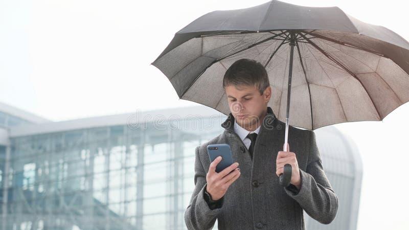 Νέα ομπρέλα εκμετάλλευσης επιχειρηματιών και χρησιμοποίηση ενός έξυπνου τηλεφώνου στο α στοκ φωτογραφίες με δικαίωμα ελεύθερης χρήσης