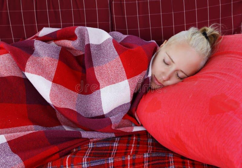 Νέα ολίσθηση γυναικών στη μεγάλη μαλακή ταλάντευση στον κήπο στο κόκκινο μαξιλάρι που καλύπτεται από το κόκκινο ελεγμένο κενό στοκ εικόνα με δικαίωμα ελεύθερης χρήσης