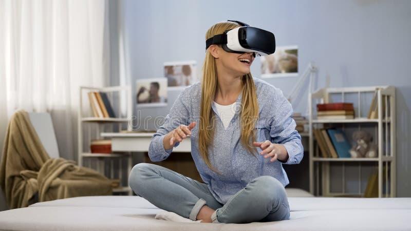 Νέα παίζοντας παιχνίδια γυναικών που χρησιμοποιούν vr τα γυαλιά κασκών στο σπίτι, που καταπλήσσουν την εμπειρία στοκ φωτογραφία με δικαίωμα ελεύθερης χρήσης