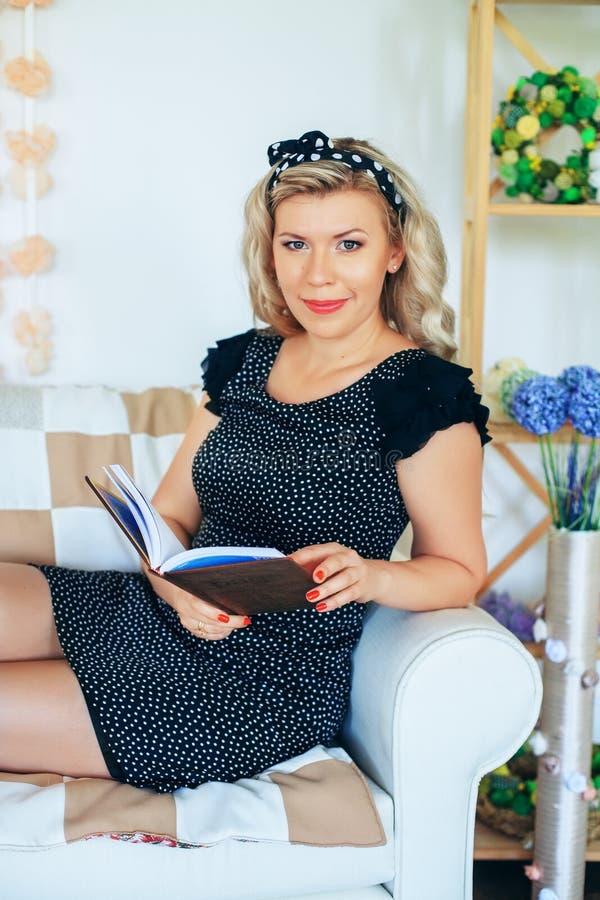 Νέα πανέμορφη ξανθή ανάγνωση ένα βιβλίο στο δωμάτιο Η έννοια στοκ φωτογραφία με δικαίωμα ελεύθερης χρήσης