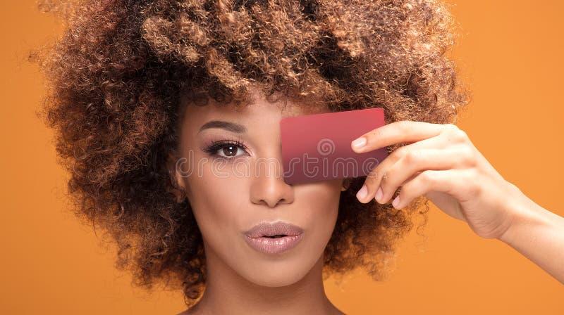 Νέα πιστωτική κάρτα εκμετάλλευσης κοριτσιών afro στο κίτρινο υπόβαθρο στοκ εικόνες